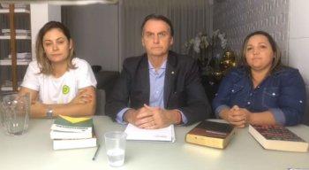 Jair Bolsonaro ao lado da esposa e de uma intérprete de libras
