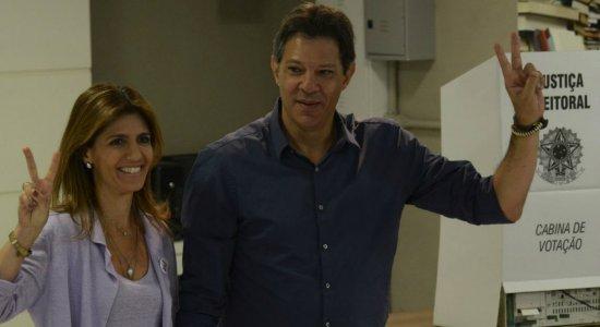 Vestido de azul e acompanhado pela esposa, Haddad vota em São Paulo