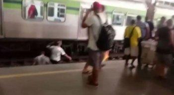 Passageiros passam perto de trem em movimento