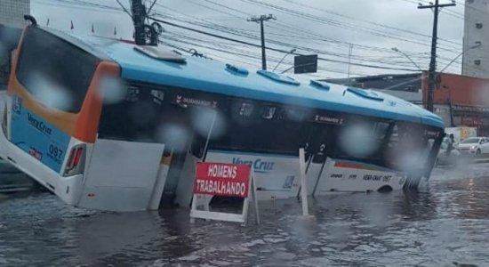 Ônibus cai em buraco por causa de alagamento em avenida na Zona Sul