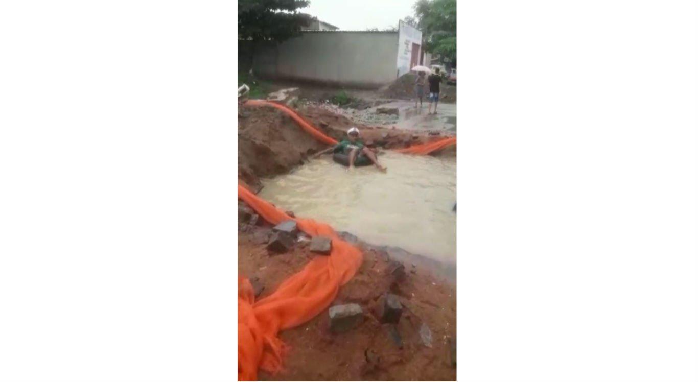 Homem boia dentro de buraco alagado no bairro João Mota, em Caruaru