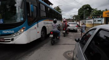 Por falta de calçadas em vias do bairro, pedestres dividem espaço com carros, motos e ônibus