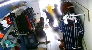 Dentro da loja, o trio manda todo mundo deitar no chão, pega objetos pessoais e muitas roupas