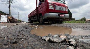 Motoristas se arriscam dirigindo entre as crateras da via