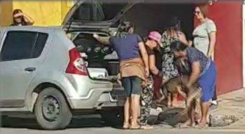 A mulher arruma o cão e depois fecha a mala e entra no carro para seguir viagem