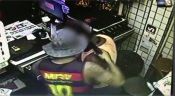 Um dos suspeitos aponta a arma para a cabeça de um funcionário no caixa da loja