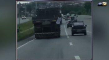 Vídeo mostra homem pendurado na traseira do caminhão