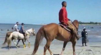 Pessoas andam com os cavalos livremente na praia de Mangue Seco, em Igarassu