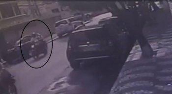 Imagens de uma câmera de segurança mostram um rapaz de camisa branca fugindo na moto