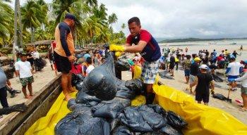 Voluntários retiram manchas de óleo do litoral pernambucano