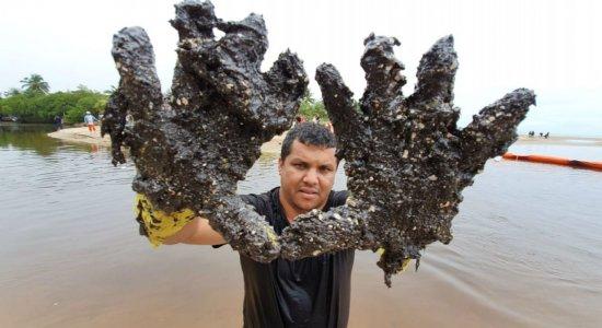 Voluntário mostra as mãos sujas de óleo