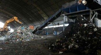 Por meio de guindastes, o material é jogado em uma gigantesca máquina trituradora, de onde sai a primeira mistura