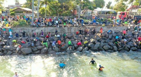 População se joga no mar e fica entre pedras para limpar óleo na praia do Janga, em Paulista
