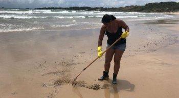 Comerciante limpa resquícios de óleo na Praia de Itapoama, local de onde tira o sustento