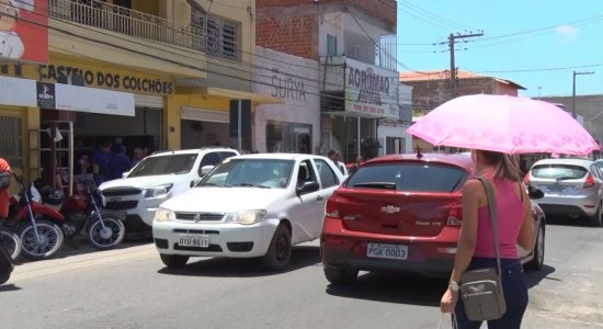 Moradores utilizam sombrinhas para se proteger do sol