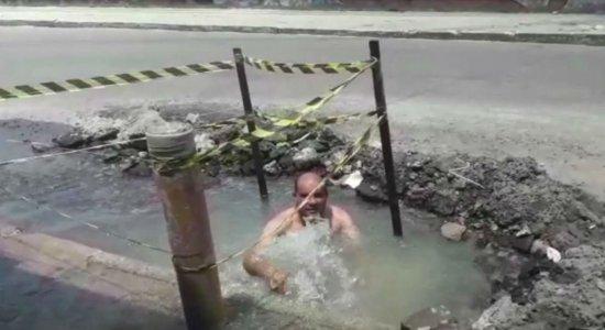 Homem toma banho dentro de buraco da Compesa na Zona Oeste do Recife