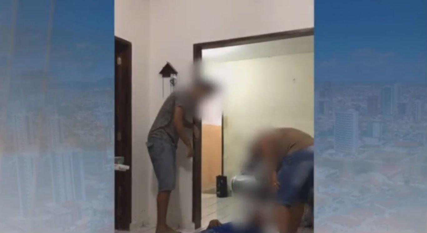 Duas pessoas derrubam a que está no meio, que cai de costas e bate a cabeça no chão