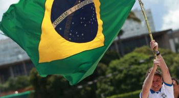 Presidente Jair Bolsonaro balança bandeira do Brasil