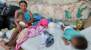 Mãe venezuelana com dois bebês em cama na calçada no Recife