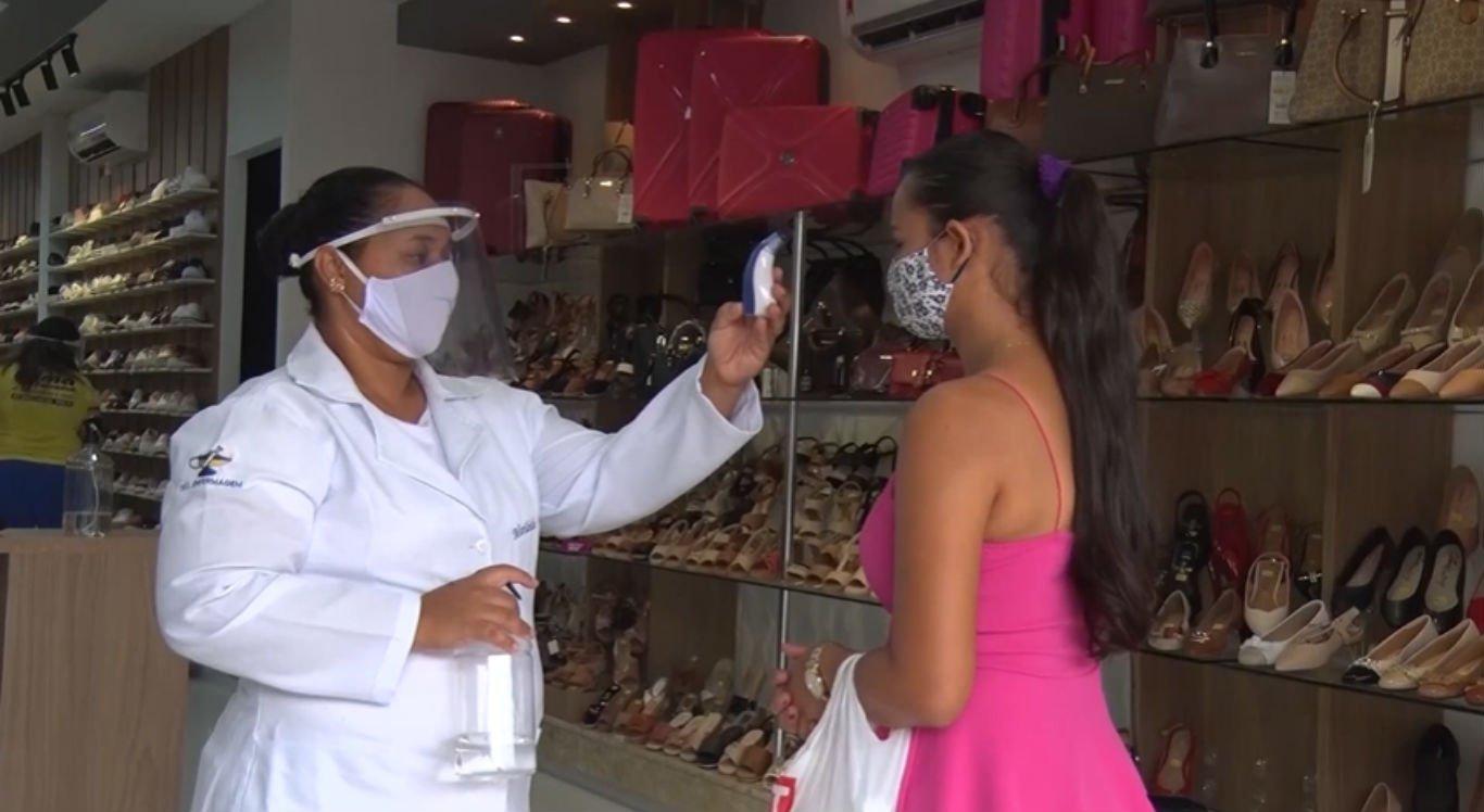 Profissional de saúde contratada por loja afere temperatura de cliente em Serra Talhada