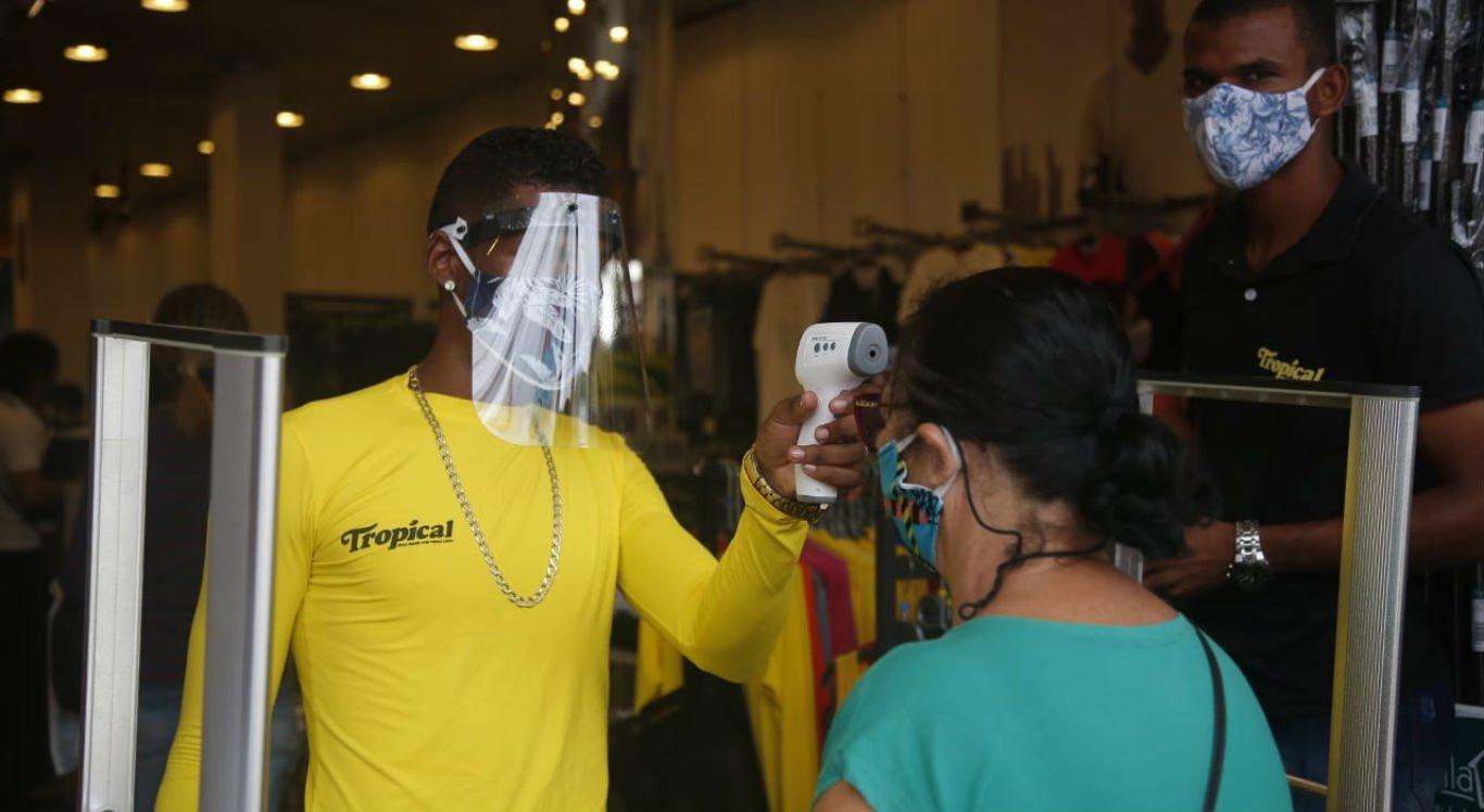 Algumas lojas aferem a temperatura dos clientes antes de deixá-los entrar