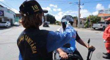 Agente da vigilância sanitária afere temperatura de motociclista em Limoeiro