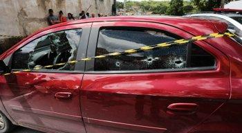 O homem estava dentro do carro vinho e foi morto com pelo menos 12 tiros