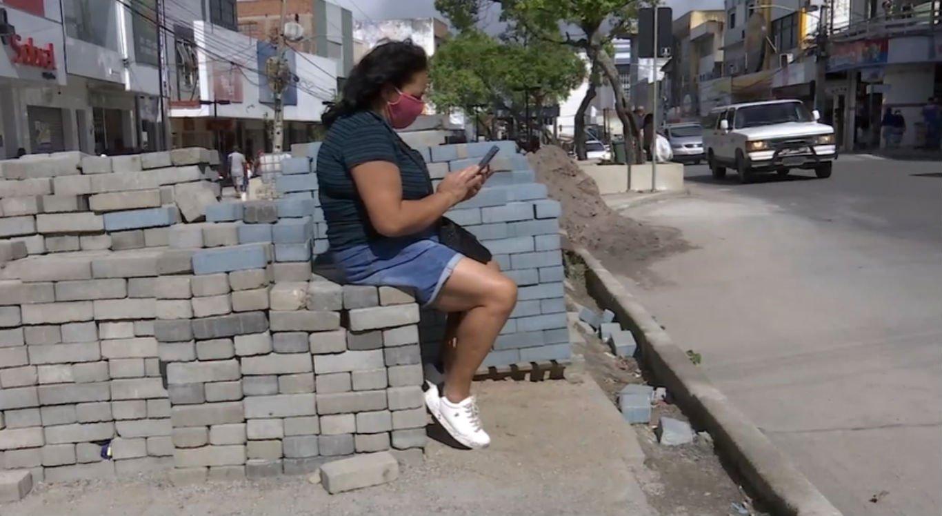 Sem bancos para se sentar, passageira de ônibus se apoia nas pedras da obra