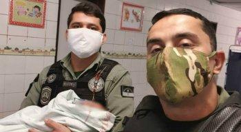 Os policiais militares, sargento De Lima e soldado Ellyson, com o bebê que foi salvo