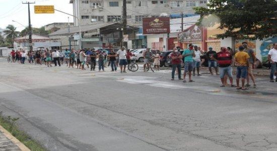 Pessoas fazem fila durante a noite em frente a agência da Caixa para sacar auxílio emergencial e FGTS em Olinda
