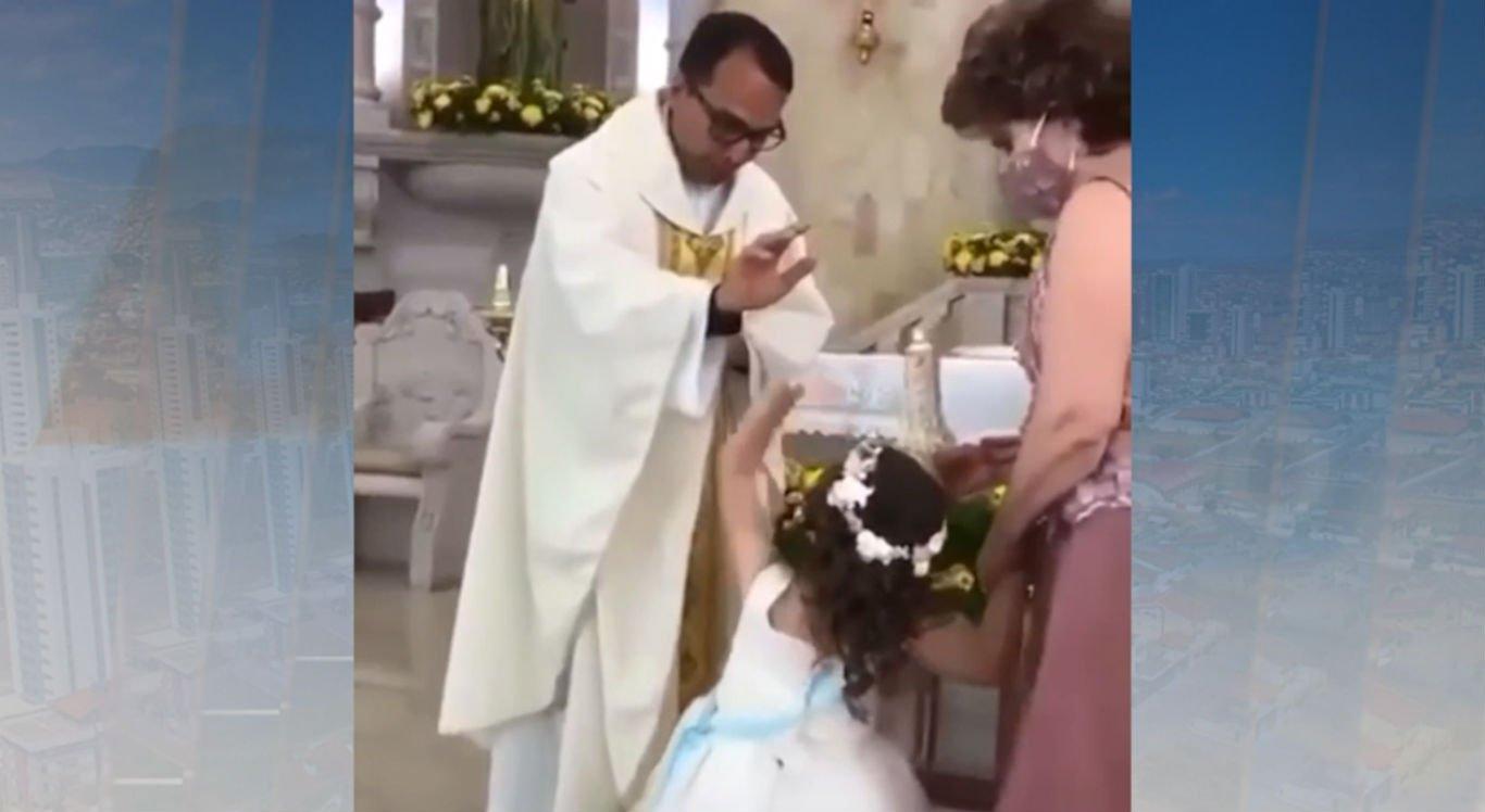 Criança se estica para tocar na mão do padre