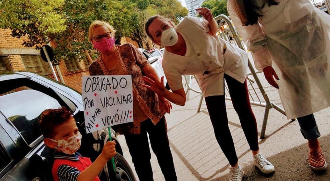Davi Rossi Rodrigues, de 5 anos, segurou um cartaz durante vacinação da avó