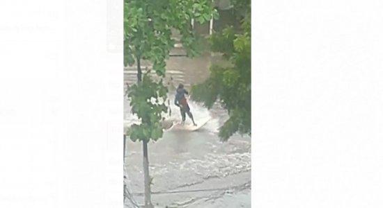 Vídeo: Homem é flagrado surfando em avenida em dia de forte chuva no Grande Recife