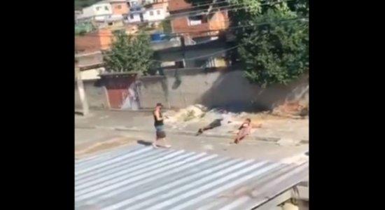 Imagens fortes mostram dois rapazes deitando no chão e sendo baleados