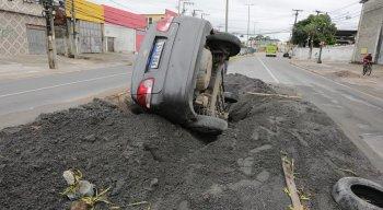 carro, um automóvel de passeio, ficou totalmente caído no buraco, apenas as rodas traseiras ficaram visíveis.