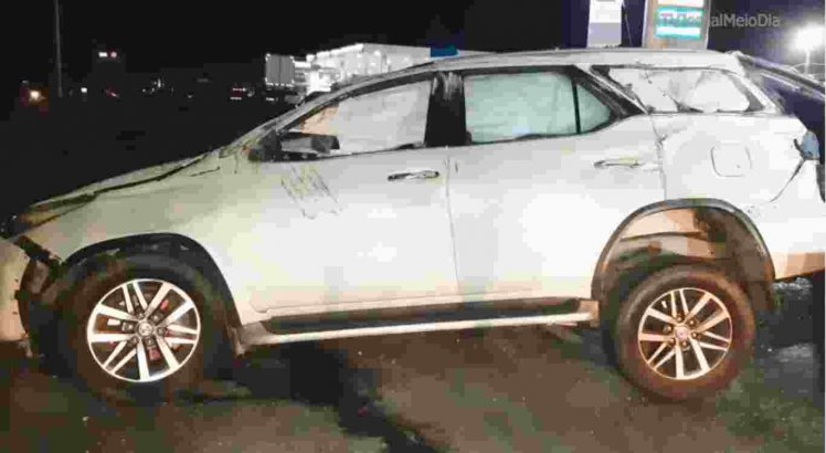 O veículo bateu em uma placa de um posto de combustível e capotou.