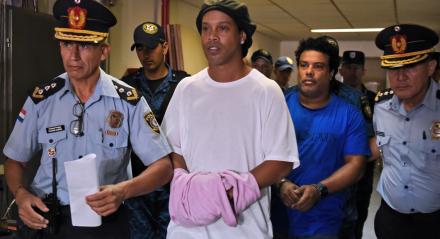 Ronaldinho (C) e seu irmão Roberto Assis (R) chegam ao Palácio da Justiça de Assunção para comparecer a um promotor público que decidirá se lhes concederá fiança ou não após sua entrada irregular no país,