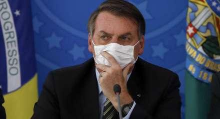 O presidente brasileiro Jair Bolsonaro (C) em conferência de imprensa relacionada ao novo coronavírus, no seu gabinete no Palácio do Planalto em Brasília, Brasil, em 18 de março de 2020