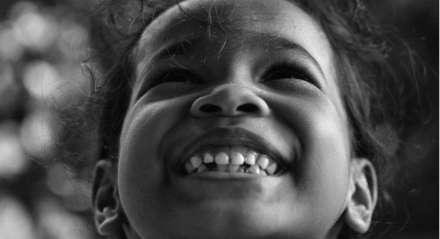 Criança sorrindo em foto preta e branca