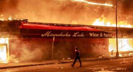 Um homem passa por uma loja de bebidas em chamas perto da Terceira Delegacia de Polícia em 28 de maio de 2020 em Minneapolis, Minnesota