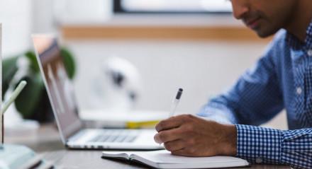 """Homem trabalhando em """"Home Office"""" com notebook e caderno"""