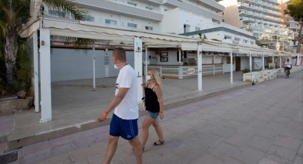 Tourists walk past closed restaurants near Magaluf Beach on the Island of Mallorca on July 27, 2020. Tour operator TUI has cancelled all British holidays to mainland Spain from today until August 9, after the UK government's decision to require travellers returning from the country to quarantine