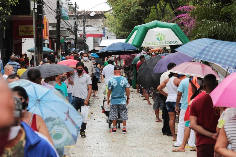 Beneficiários enfrentam chuva e se aglomeram em filas para saque do auxílio emergencial em Jaboatão