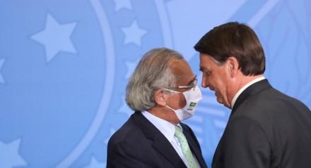 """DF - CORONAVÍRUS/CRISE/CRÉDITO - ECONOMIA - O presidente da República, Jair Bolsonaro (d), e o ministro da Economia, Paulo Guedes, durante a solenidade de sanção de medidas provisórias de facilitação de acesso ao crédito, no Palácio do Planalto, em Brasília, nesta quarta-feira, 19. Segundo Guedes, os dois programas sancionados hoje (de crédito para a folha de pagamentos e para pequenas e médias empresas) são """"praticamente"""" as últimas medidas lançadas para fomentar o crédito diante do cenário de pandemia.  Foto: GABRIELA BILó/ESTADÃO CONTEÚDO"""