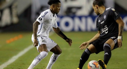 Brazil's Santos forward Marinho (L) and Paraguay's Olimpia midfielder Willian Candia vie for the ball during their closed-door Copa Libertadores group phase football match at the Vila Belmiro stadium in Santos, Brazil, on September 15, 2020, amid the COVI