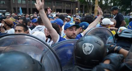 Torcedores de Diego Maradona discutem com a polícia para entrar na Casa do Governo para homenagear a lenda do futebol