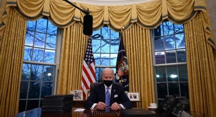 O presidente dos Estados Unidos, Joe Biden, segura uma caneta enquanto se prepara para assinar uma série de ordens no Salão Oval da Casa Branca em Washington