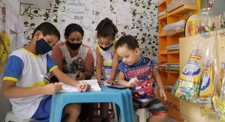 Maria Santos mãe de quatro filhos improvisou um cantinho de estudos na sala onde vende pipoca e confeito para complementar a renda